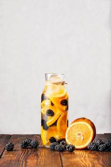 Garrafa de água com infusão de laranja crua fatiada e amora fresca. ingredientes na mesa de madeira.
