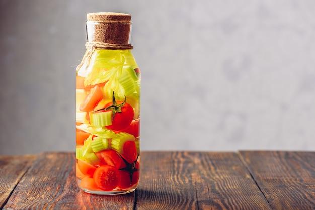 Garrafa de água com infusão de tomate cereja e talos de aipo