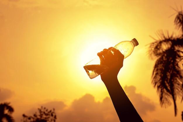 Garrafa de água de identificador de silhueta com fundo por do sol