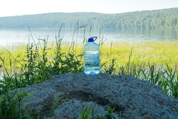 Garrafa de água de nascente perto da margem do lago