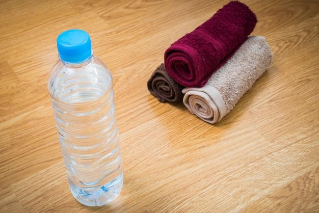 Garrafa de água de plástico e toalha na mesa de madeira