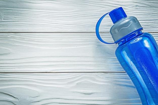 Garrafa de água de plástico no conceito de fitness da placa de madeira