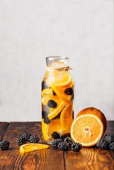 Garrafa de água desintoxicante com infusão de laranja crua fatiada e amora fresca