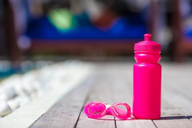 Garrafa de água desportiva rosa perto da piscina