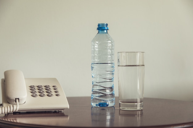 Garrafa de água e copo com telefone na mesa