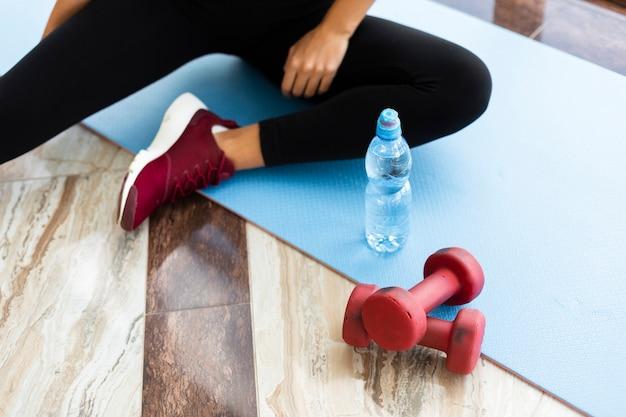 Garrafa de água e pesos no tapete de ioga