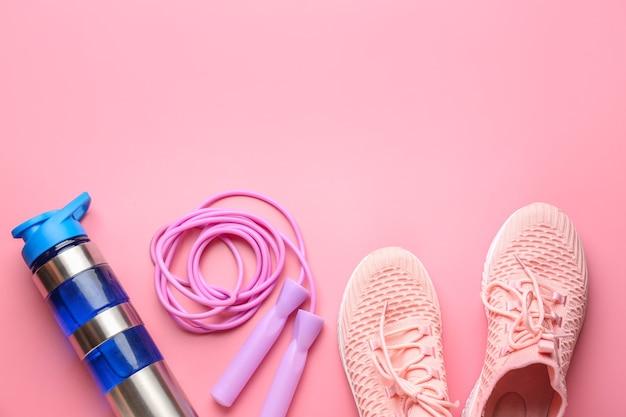 Garrafa de água esportiva, sapatos e pular corda em fundo rosa