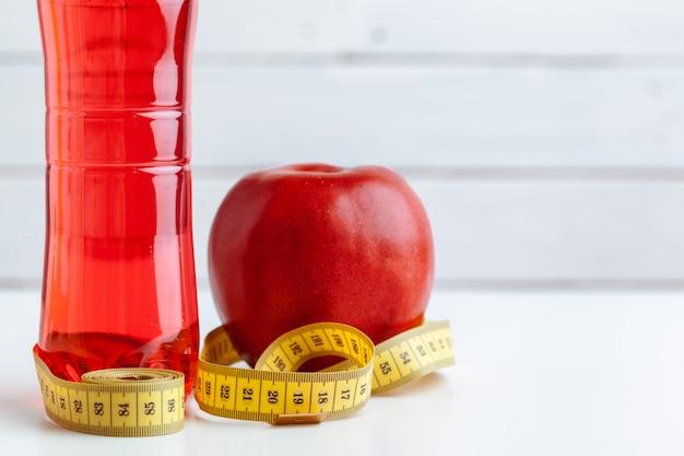 Garrafa de água, fita métrica e maçã fresca em cima da mesa