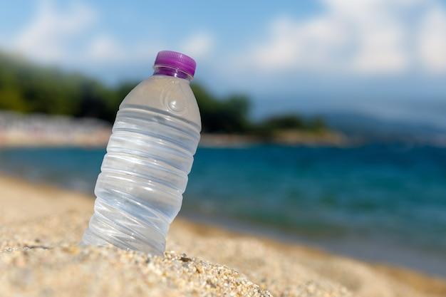 Garrafa de água fresca gelada na areia da praia
