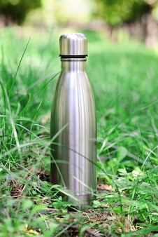 Garrafa de água garrafa térmica de aço reutilizável na grama verde