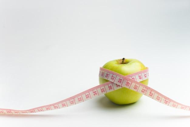 Garrafa de água, maçã e fita métrica, isolada no fundo branco