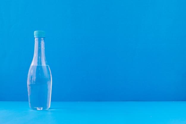 Garrafa de água mineral sobre fundo azul.
