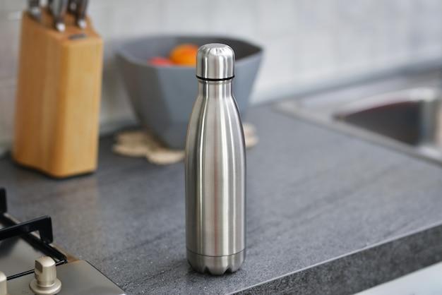 Garrafa de água na mesa da cozinha garrafa de água térmica de aço
