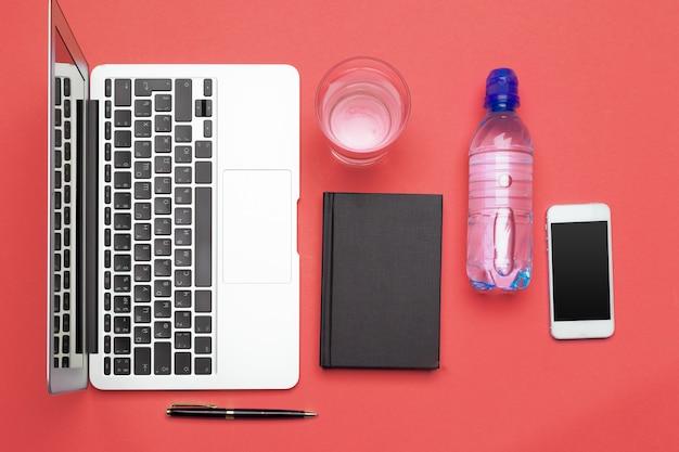 Garrafa de água na mesa de escritório perto de laptop