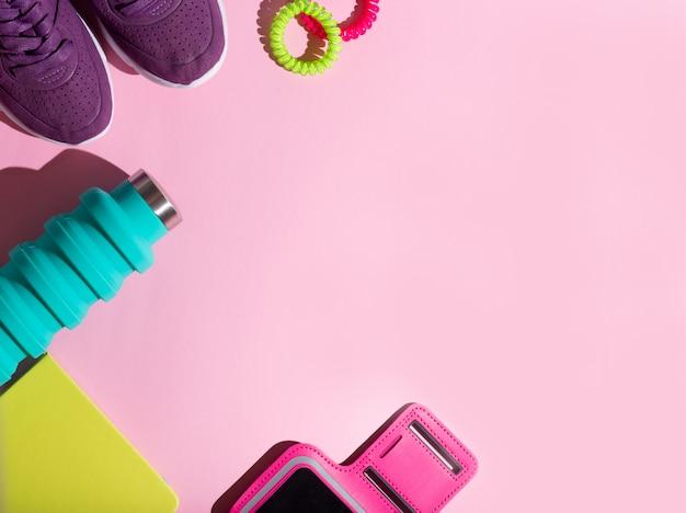 Garrafa de água plana esporte leigos correndo fitness, faixa elástica rosa, diário verde, suporte de telefone e tênis roxos em um fundo rosa