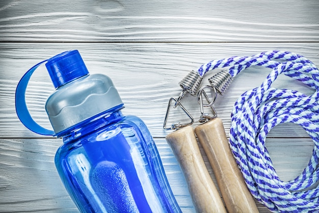 Garrafa de água plástica para pular corda na placa de madeira conceito de fitness