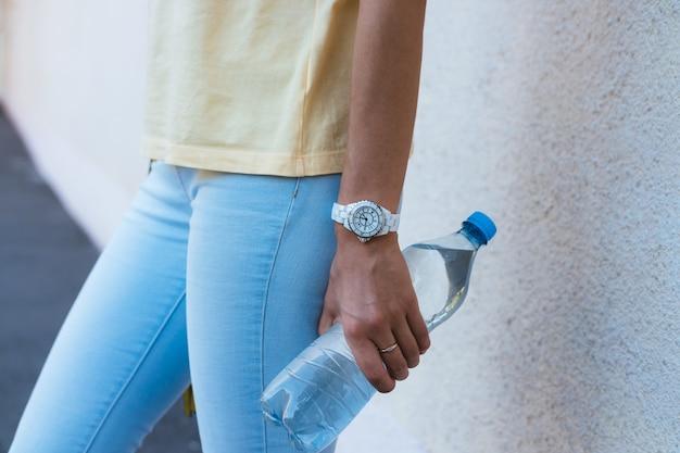 Garrafa de água potável em um close de mão feminina