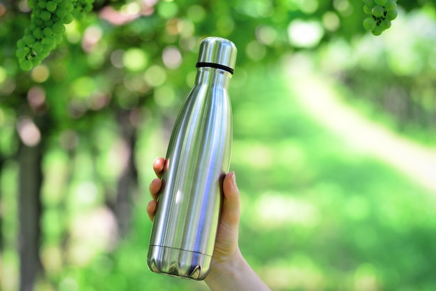 Garrafa de água reutilizável de aço inoxidável no fundo do vinhedo