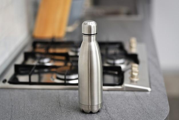 Garrafa de água reutilizável de aço inoxidável no interior do apartamento com cozinha branca