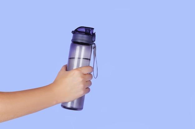 Garrafa de água reutilizável na mão de um homem sobre fundo azul. copyspace