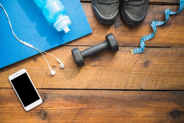 Garrafa de agua; sapatos esportivos; fone de ouvido; celular; halteres e fita métrica em fundo de madeira