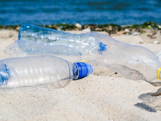 Garrafa de águas residuais vazia na areia na praia