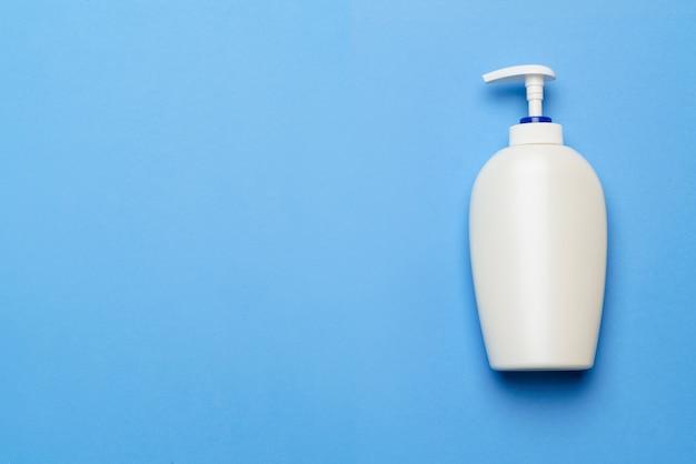 Garrafa de álcool anti-séptico mão higienizar spray sobre um fundo azul para a prevenção de coronavírus - layout plano com espaço da cópia