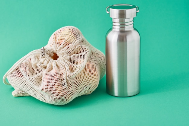 Garrafa de alumínio e frutas em saco natural sobre fundo verde. eco amigável itens close-up. zero conceito de resíduos