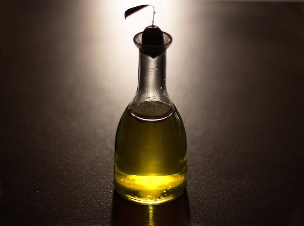 Garrafa de azeite com azeitona com fundo preto