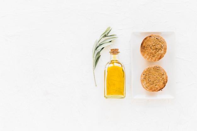 Garrafa de azeite com uma fatia de pão no fundo branco
