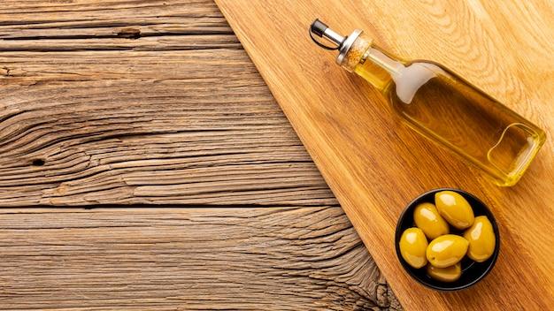 Garrafa de azeite e azeitonas amarelas com espaço de cópia