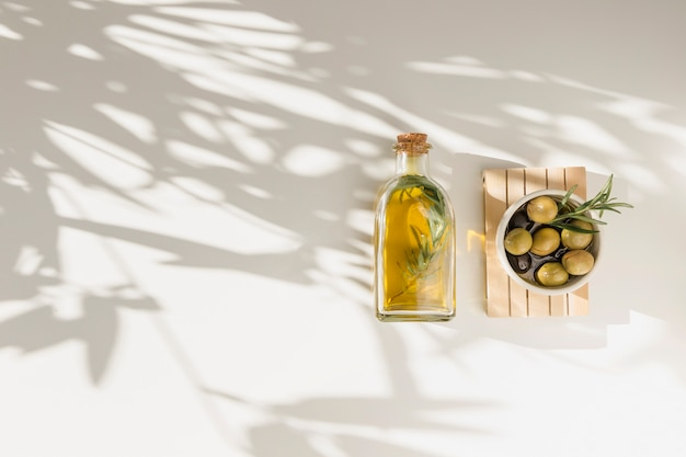 Garrafa de azeite e tigela de azeitonas na placa de madeira sobre o fundo branco