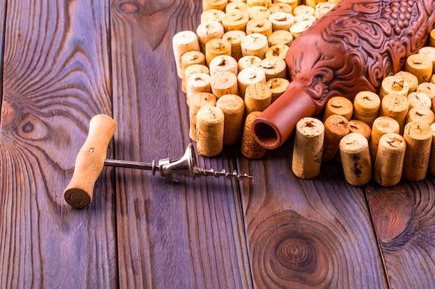 Garrafa de barro, saca-rolhas de metal e cortiça em uma mesa de madeira.