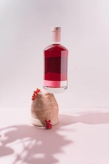 Garrafa de bebida alcoólica em vaso antigo e rústico com frutas vermelhas em fundo pastel.