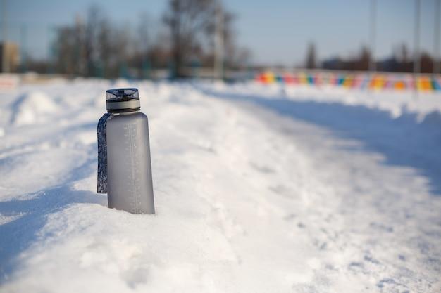 Garrafa de bebida plástica cinza cinza na neve