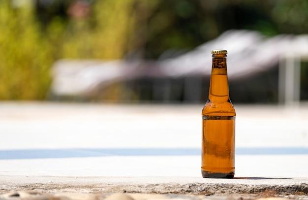 Garrafa de cerveja à beira de uma piscina.