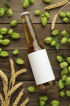 Garrafa de cerveja com cones de lúpulo e trigo em fundo cinza, close-up. foto vertical
