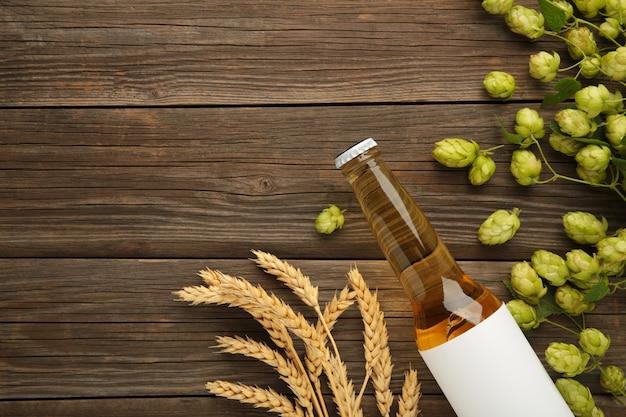 Garrafa de cerveja com cones de lúpulo e trigo em fundo cinza, close-up.