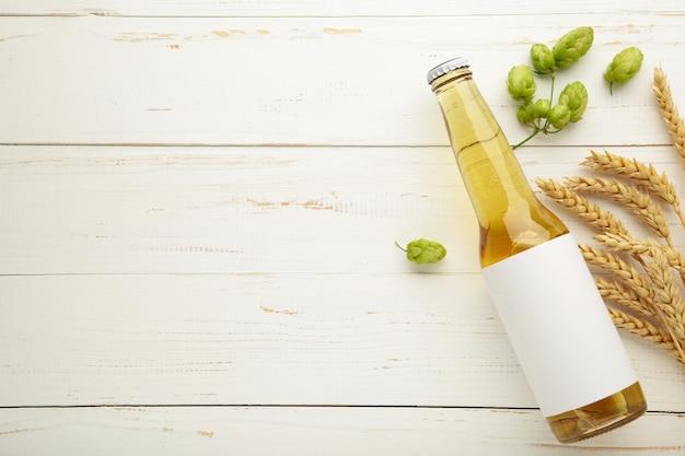 Garrafa de cerveja com cones de lúpulo e trigo no fundo branco, close-up. vista do topo