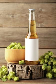 Garrafa de cerveja com cones de lúpulo em fundo cinza, close-up. foto vertical