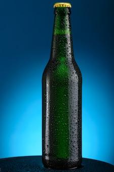 Garrafa de cerveja com gotas isoladas em fundo azul