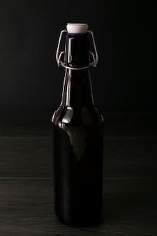 Garrafa de cerveja elegante vista frontal em fundo escuro