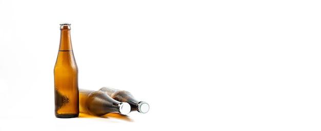 Garrafa de cerveja em um fundo branco; conjunto de garrafas de cerveja com gotas de água no fundo branco