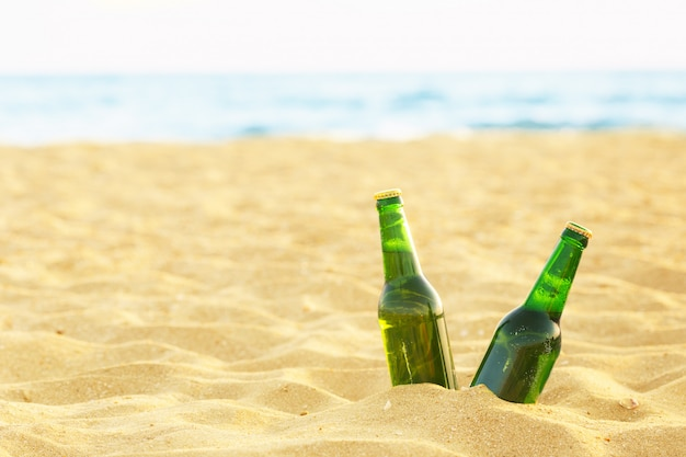 Garrafa de cerveja em uma praia arenosa