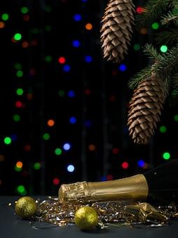 Garrafa de champanhe com balões amarelos debaixo de uma árvore de natal. feliz ano novo