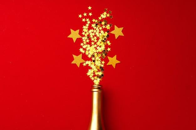 Garrafa de champanhe com confete cintilante em plano vermelho