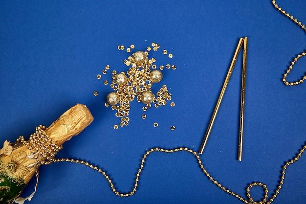 Garrafa de champanhe com confetes dourados sobre fundo de papel azul.