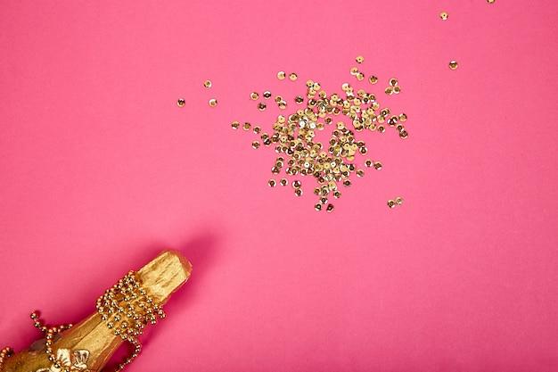 Garrafa de champanhe com confetes dourados sobre fundo de papel rosa.