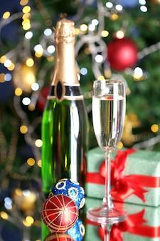 Garrafa de champanhe com copo e bolas de natal no fundo da árvore de natal