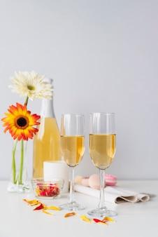 Garrafa de champanhe com copos e flores